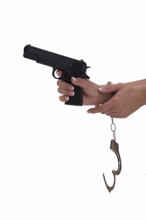 incarcerated: womans hand with handcuffs and gun on a white background Stock Photo