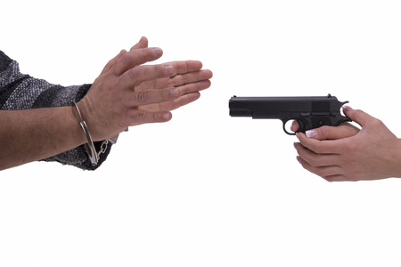 incarcerated: hands of woman and man with gun and handcuffs on a white background