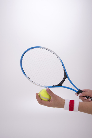 Woman hands with tennis racket on a white background