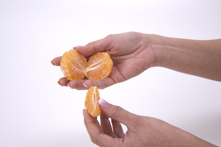 woman holding slices of mandarin Stock Photo