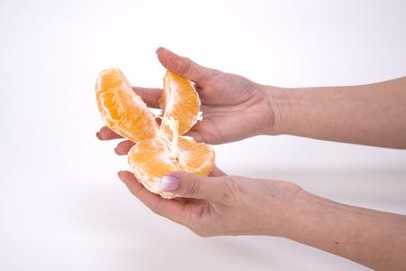 白い背景にオレンジのスライスを保持している女性