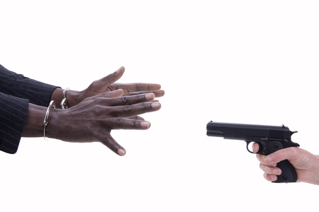 incarcerated: Woman hands with the gun and hands of man surrenders Stock Photo