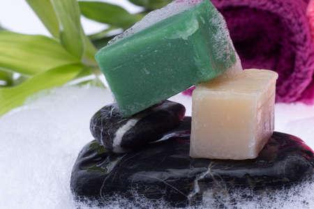 bath soap and foam on a black stone base on a white background