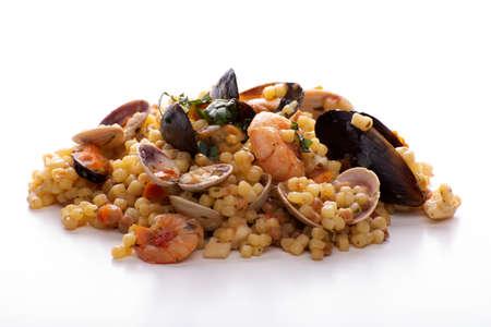 Sardinian fregola with seafood on a white background
