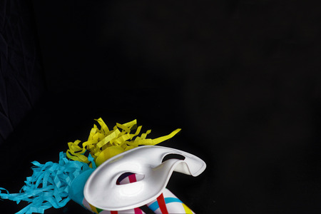 white carnival mask with multicolored tinsel on a black background Stock Photo