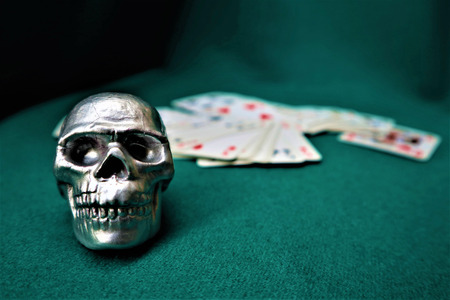 Small decorative silver human skull with playing cards on a green table