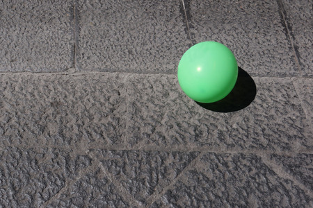 green balloon on lava stone pavement