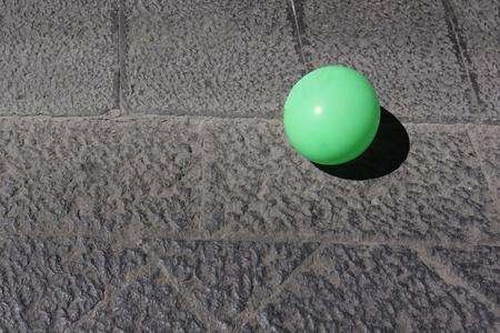 green balloon on lava stone pavement