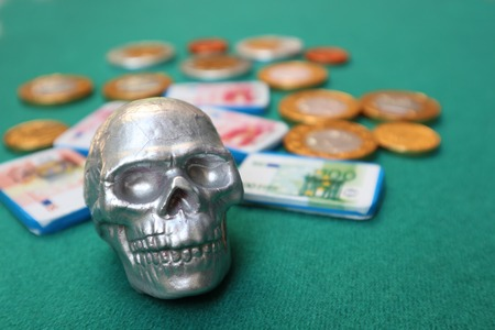 Small decorative silver human skull with money on green table