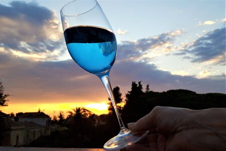 Photo of female hand with glass of a trendy blue wine