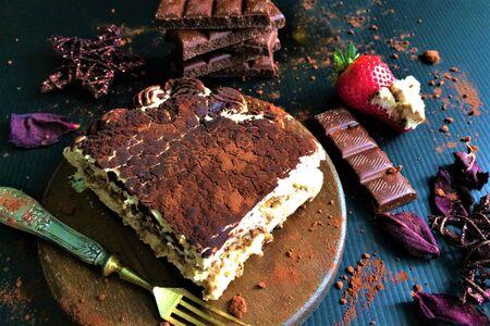 Tasty sliced tiramisu on a wooden board with fork, chocolate, strawberry