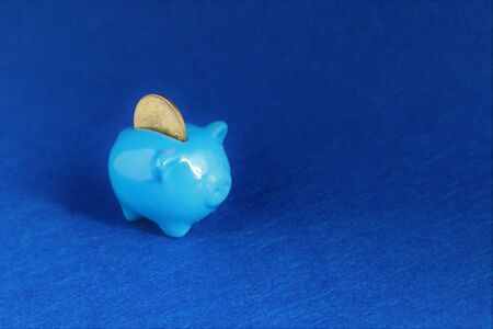 Blue Piggy bank with coin in trendy color of year 2020 on classic blue background. Saving investment, financial money, banking concept. Copy space.