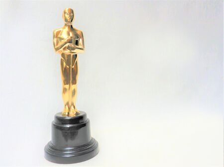 The golden statue of Oscar on a white background. Success and victory concept