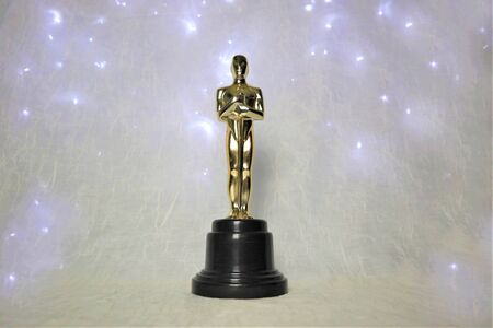 The golden statue of Oscar on a white background, with illumination around a prestigious figure. Success and victory concept