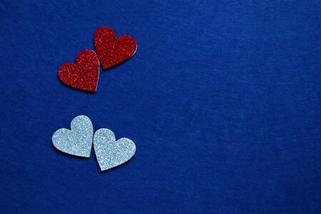 two red and two silver hearts on classic blue background in trendy color of year 2020. Copy space
