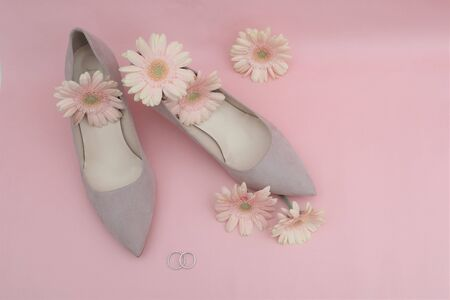 wedding concept. gerbera flowers, rings, beige shoes on a pink background.  Top view. Copy space