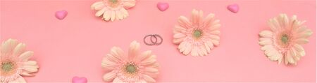 wedding concept. gerbera flowers, hearts, rings, a pink background. Top view.