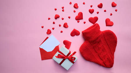 red knitted heart with many red hearts and an envelope on a pink background. copy space. banner Valentine's day greeting card. love concept. flat lay 版權商用圖片