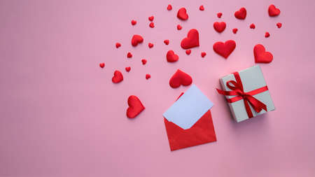 many red hearts, an envelope and a gift on a pink background .. copy space. banner Valentine's day greeting card. love concept. flat lay