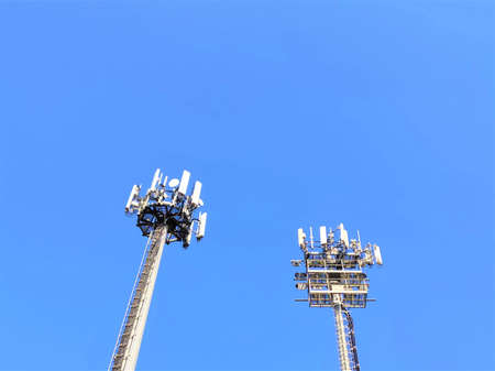 Telecommunication tower with antennas against blue sky background with copy space. Telecommunication tower of 4G and 5G cellular. Cell Site Base Station. Wireless Communication Antenna Transmitter. 版權商用圖片