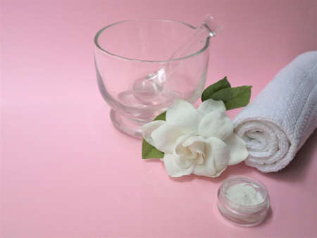 Spa setting and Spa background composition with white gardenia flower on pink background. Towel, candles, flowers, stones. Massage, oriental therapy, wellbeing and meditation.