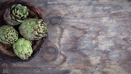 artichokes on a wooden background. view from above. Copy space banner. flat lay