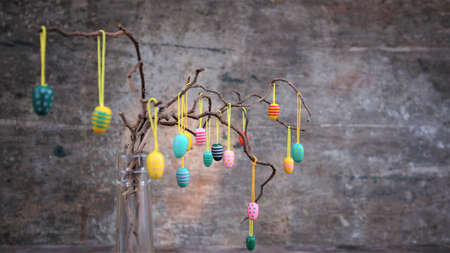 Easter dekorative eggs on tree branches. Easter tree in vase with colorful eggs on a gray rustic background