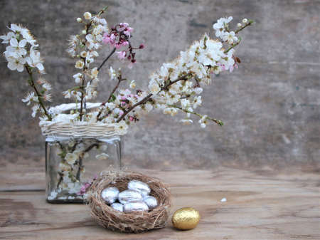 Blooming spring branch and easter eggs. Easter horizontal background. Pink and white cherry blossom twigs on gray background, easter scene