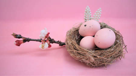 Easter composition with eggs and rabbit ears made of small pearls on pink pastel background. Branch of blossoming sakura. Happy easter. Flat Lay. Copy space