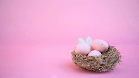 Easter composition with eggs and rabbit ears made of small pearls on pink pastel background. Happy easter. Copy space