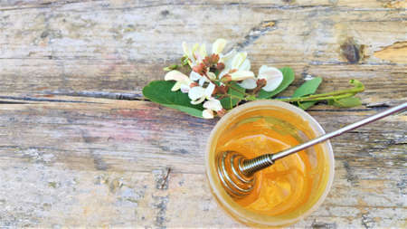 Acacia honey and flowering acacia on wooden table. Acacia flowers and honey jar top view. Acacia honey, acicia flowers and wooden honey spoon Standard-Bild