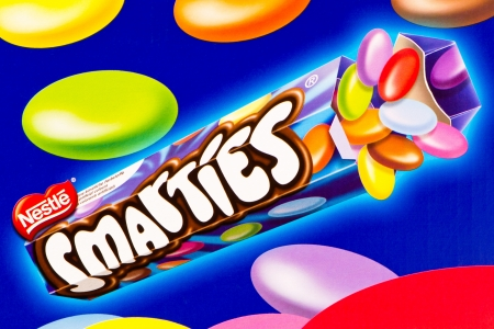 nestle: Arad, Romania - April 8, 2012: Tube of Nestle Smarties printed on cardboard. Nestle Smarties are a colour-varied sugar-coated chocolate confectionery. Studio shot.