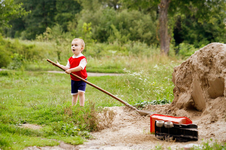 imitate: Countryside. Little boy holding a big shovel in his hands. He plays in the sand, to imitate adults. Stock Photo