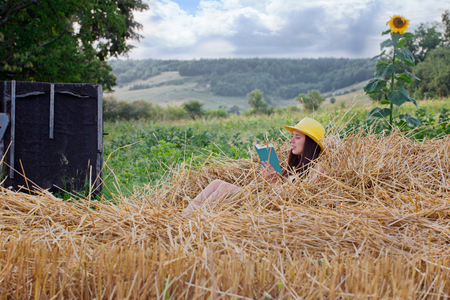well read: Village. Young girl in a straw hat sitting on straw and reading a book. Right growing sunflower. On the left is the old well. Stock Photo