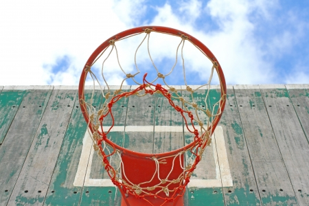 Old wooden basketball hoop on blue sky photo