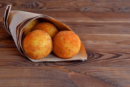 Arancini balls. Fried rice balls in paper on brown wooden background. Snack, sicilian street food Stock fotó