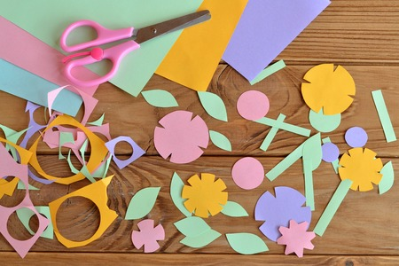 Paper flowers, paper sheets, scissors, paper scrap on a wooden table. Paper flower craft for kids. Childrens art project