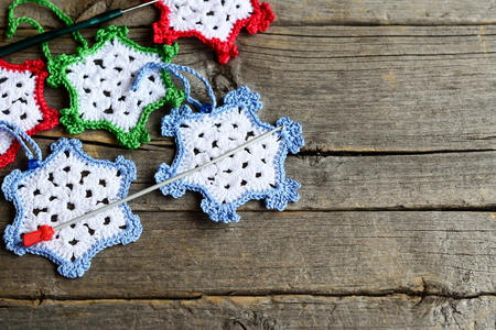 crocheted: Crocheted snowflakes, two hooks on an old wooden background with blank copy space for text. Simple winter crafts for kids and beginners. Crochet home decorations Stock Photo