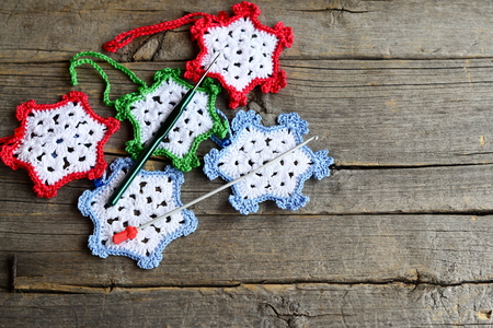 crocheted: Snowflakes crocheted from cotton yarn, two hooks on an old wooden background with copy space for text. Easy winter crafts for children and beginners. Crochet home ornaments Stock Photo