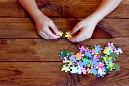 segmented bodies: Child connects puzzles. A lot of puzzles on wooden table