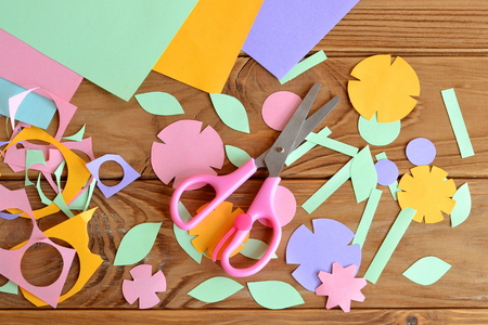 Papieren bloemen, vellen papier, schaar, papier schroot op een houten tafel. Papierbloembak voor kinderen. Kunstproject voor kinderen