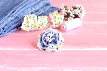 needle laces: Nice flower brooch made from recycled old jeans, lace and artificial stamens. Summer flower denim brooch, jeans, thread, needles, pins, lace on pink wooden background. Art hobby for kids and women Stock Photo