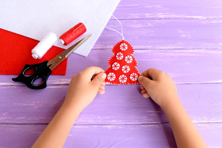 Child holds Christmas tree ornament in his hands. Red felt tree with white balls, scissors, thread, needle, felt sheets on lilac wooden background. Christmas sewing idea