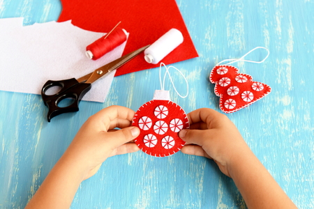 Child holds a Christmas tree ball in his hands. Embroidered red and white ball ornament. Felt sheets, thread, needle, scissors on a blue wooden background. Child doing Christmas crafts Stock Photo