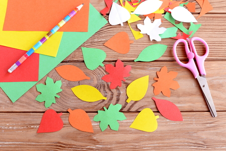 Autumn colorful leaves cut from paper, pencil, scissors, colored paper sheets on a wooden background. Teaching scissor cutting. Early learning in kindergarten and at home. Kids art Stock Photo - 65749690