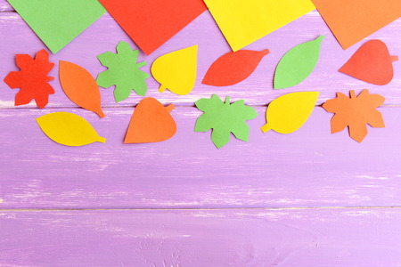 Autumn leaves cut from colored paper. Yellow, red, green, and orange paper leaves on blue wooden background with blank space for text. Easy fall crafts for kids. Top view