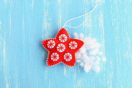 learning by doing: Stuff the felt Christmas star with hollowfiber. Christmas sewing craft. Red hanging star ornament decorated with white balls on a blue background. How to teach a child to sew. Tutorial. Step. Top view Stock Photo