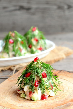 Christmas tree salad. Salad with meat, champignons, cucumbers and eggs decorated with dill and pomegranate. Creative Christmas salad decoration idea for inspiration. Homemade recipe. Old wooden table