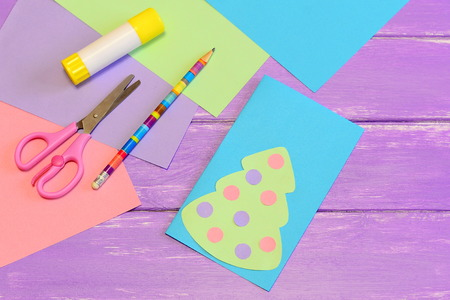 How to make easy Christmas card from colored paper. Step. Colored paper set, scissors, pencil, greeting card with Christmas tree, glue stick. Inspiration for kids of all ages. Winter children activity