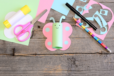 Funny paper butterfly, scissors, marker, glue stick, colored paper sheets and scraps, pencil on old wooden table. Children workplace. Summer children art craft project in kindergarten, camp or home 版權商用圖片